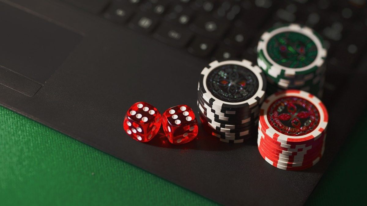 poker chips and dice on a computer to symbolize how to start an online casino